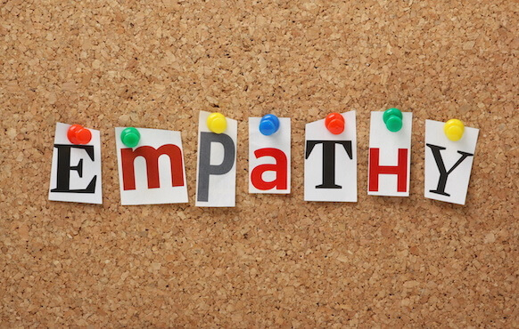 The image shows magazine cut outs of the letters E M P A T H Y pinned to a cork board. Empathy is a great tool to help facilitate a discussion between employees in conflict.